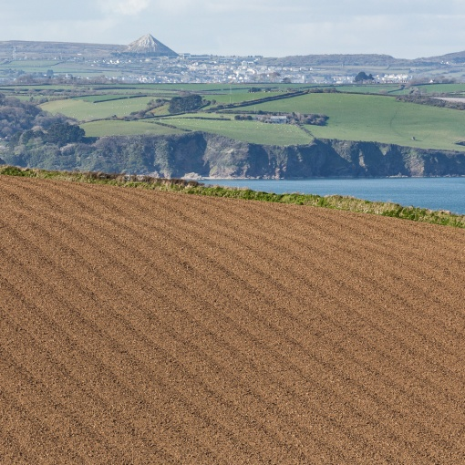 Corduroy fields, Chapel Point. On the horizon Sky Tip or Great Treverbyn Tip near St Austell made from dumped china clay, Cornwall.