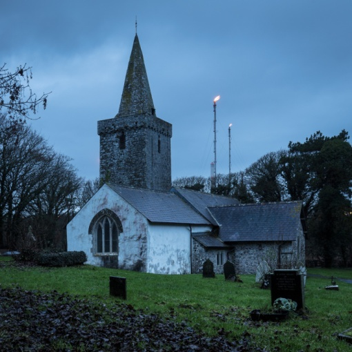 St Mary's Church with Pembroke Oil Refinery Flares, Pwllcrochan, Dyfed.